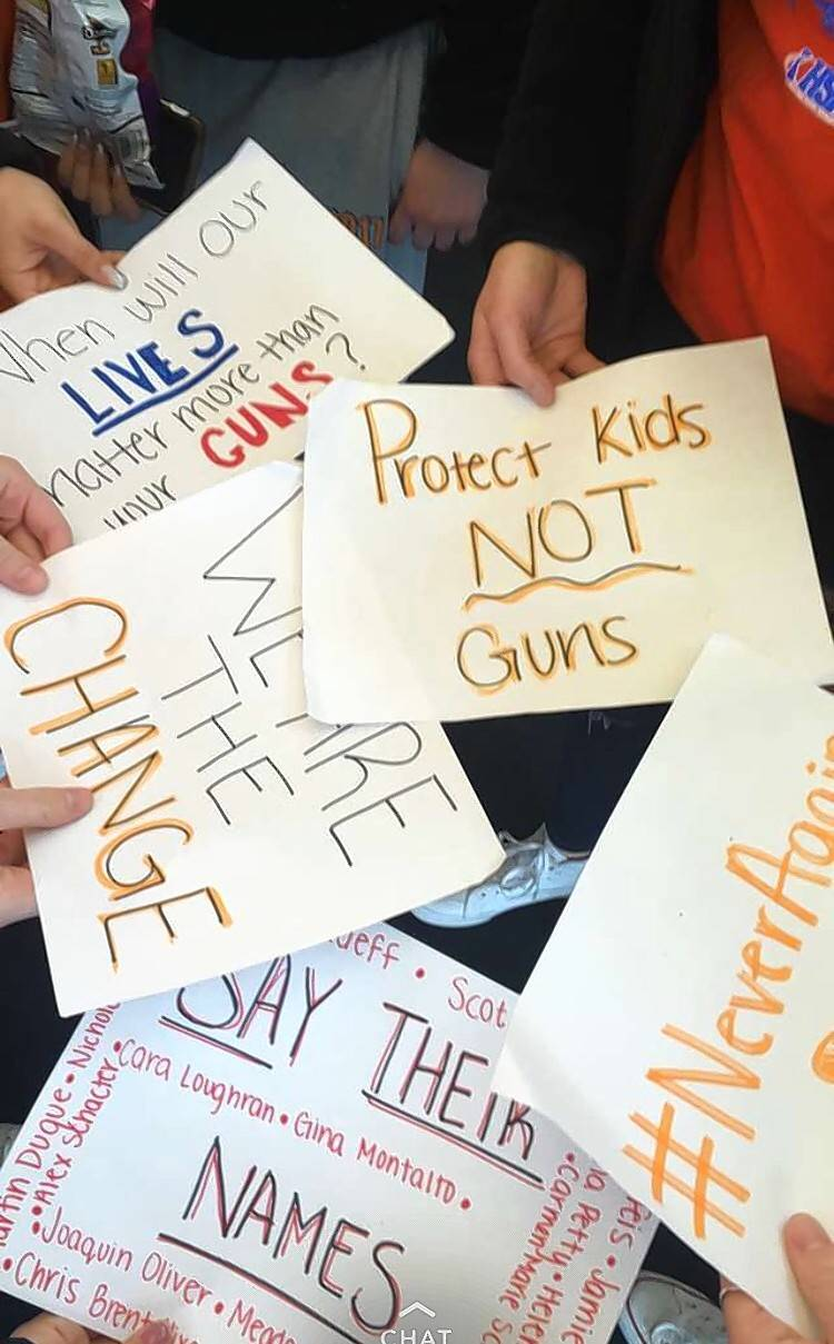 Hoffman Estates High School students prepare signs advocating for tighter gun control measures before a walkout held Wednesday, one week after the killing of 17 students and staff at a Florida high school.