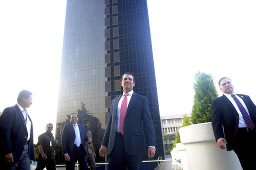 "The eldest son of U.S. President Donald Trump, Donald Trump Jr. , center, stands in front of Trump Towers after its inauguration in Pune, India, Wednesday, Feb. 21, 2018. Donald Trump Jr. said any talk that his family was profiting from his father's presidency was ""nonsense"" as he began a visit to India to promote real estate deals that bear his family's name."