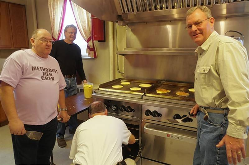 United Methodist Men Bob Koenegstein, back.left, Jim Dean, front left, Chris Jeffreys, right, and Steve Belcher, back to camera, prepare oven-baked Johnsonville Sausage Links and fresh, hot pancakes for the congregation as a warm-up for last year's Annual Methodist Men's Pancake Breakfast.