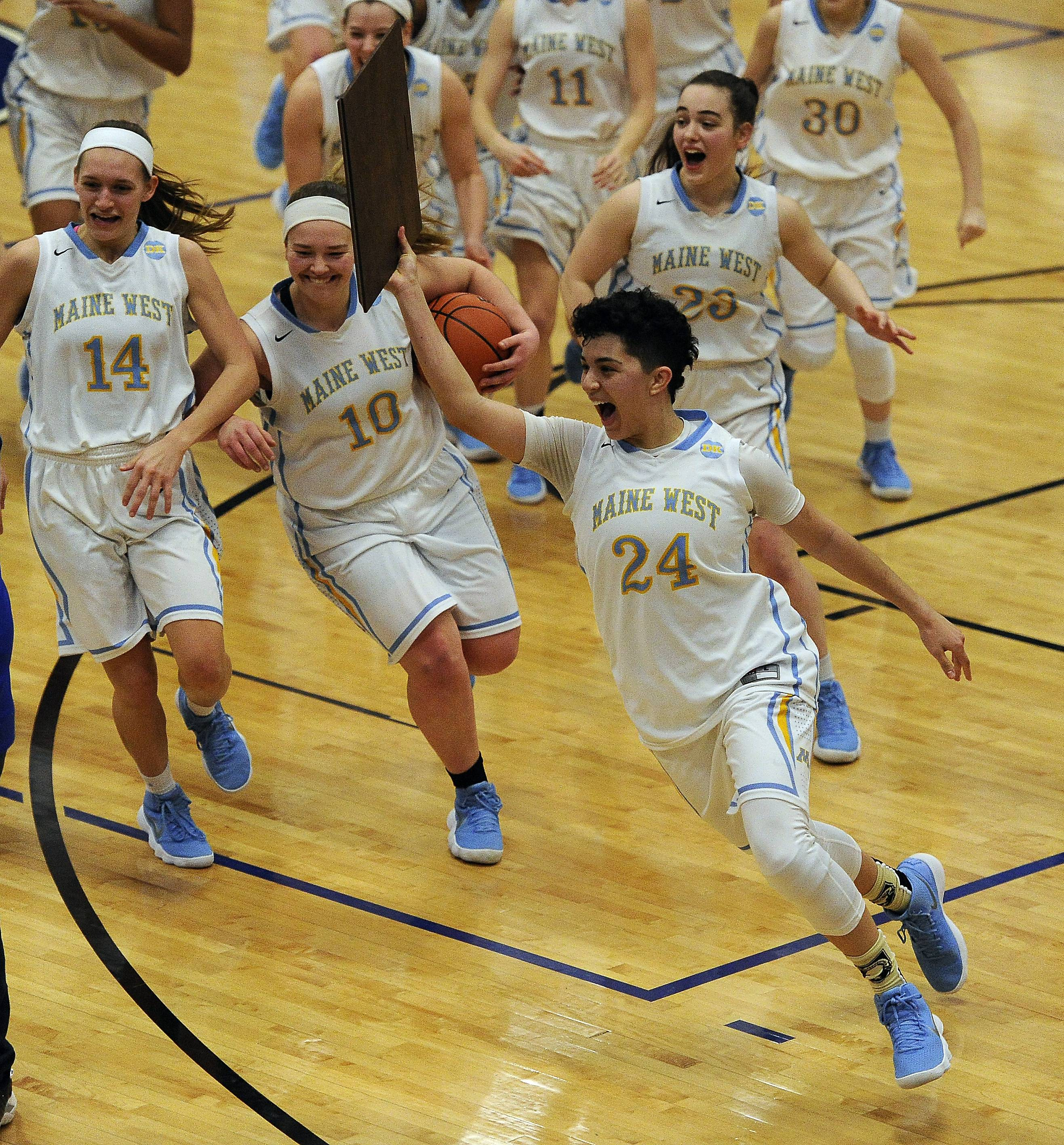 Maine West guard Alisa Fallon holds up the championship plaque, running with teammates in tow after the Warriors' victory in the Class 4A sectional championship game at Maine East.
