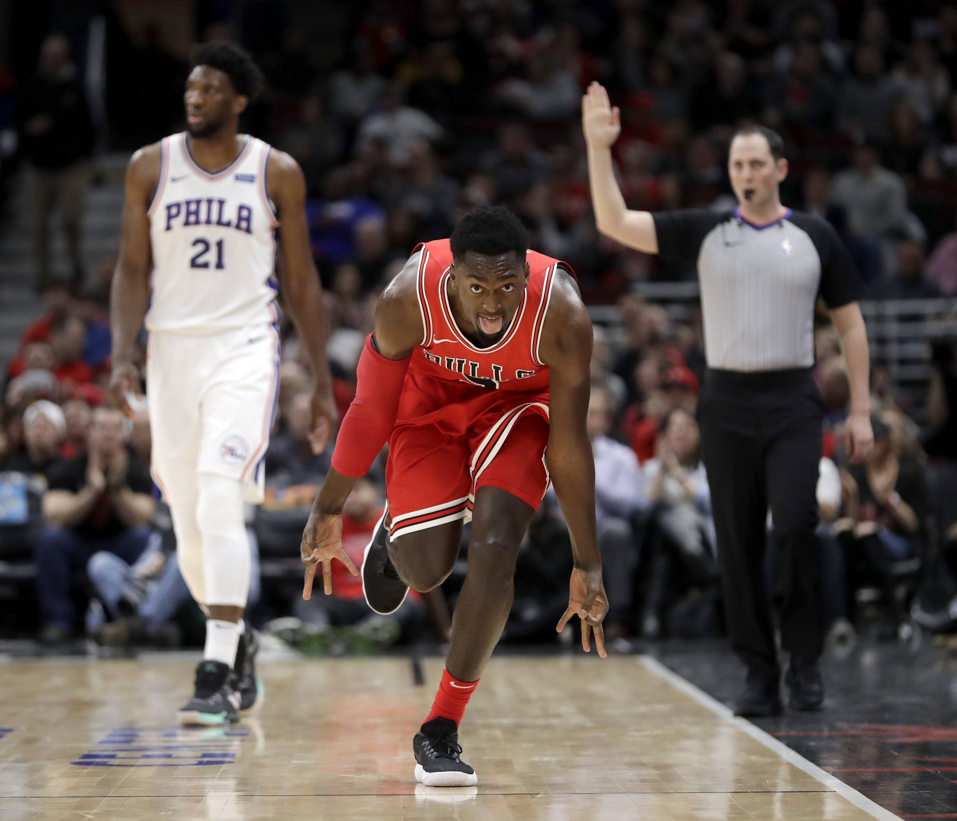 Chicago Bulls' Bobby Portis reacts after scoring a three-point shot over Philadelphia 76ers' Joel Embiid, left, during the first half of an NBA basketball game Thursday, Feb. 22, 2018, in Chicago. (AP Photo/Charles Rex Arbogast)