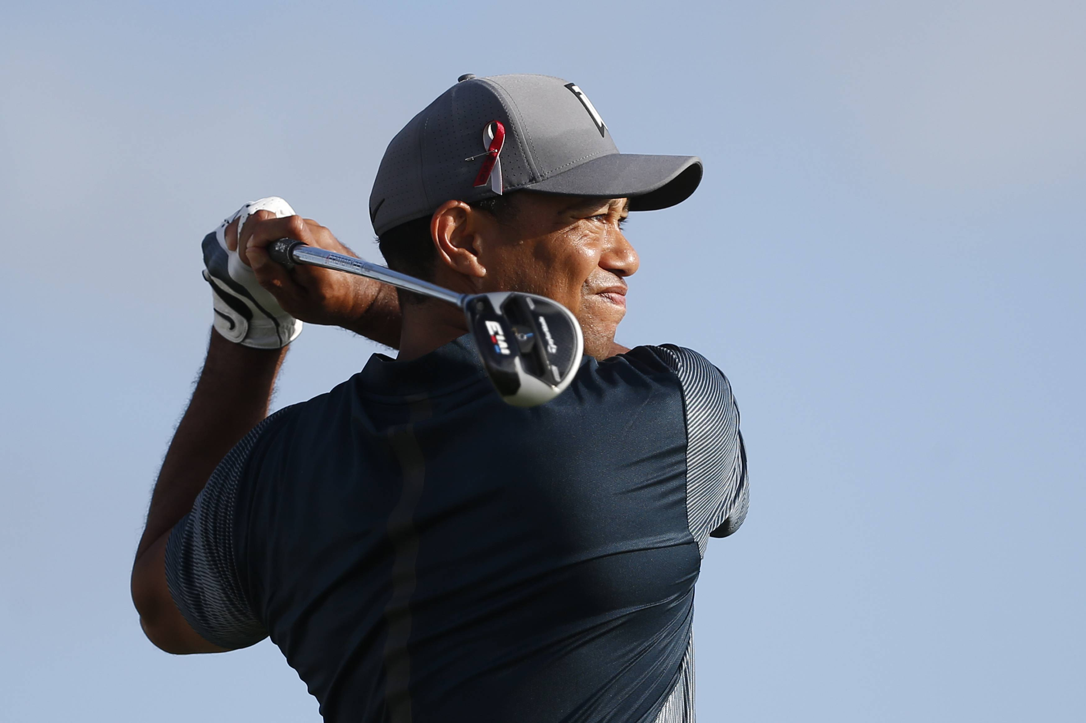 Tiger Woods tees off on the 13th tee during the first round of the Honda Classic golf tournament on Thursday in Palm Beach Gardens, Fla. Golfers wore a ribbon on their caps in memory of the students and faculty killed in the Marjory Stoneman Douglas High School shooting.