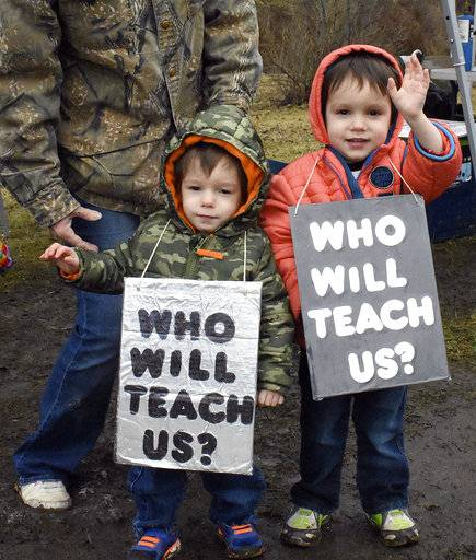 Twins, Corbin and Cameron Myers, 3, wave to supporters that honk as they past the teachers protest near North Marion High School, in Rachel, W.Va., on Thursday, Feb. 22, 2018. West Virginia public school teachers launched a statewide walkout Thursday that canceled classes in all 55 counties, protesting over pay hikes signed by the governor hours earlier that the teachers say don't go far enough. (Tammy Shriver/Times-West Virginian via AP)
