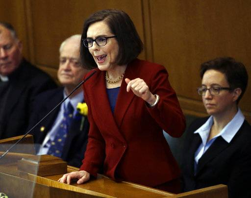 FILE - In this Jan. 9, 2017, file photo, Oregon Gov. Kate Brown delivers her inaugural speech in the Capitol House chambers in Salem, Ore. People convicted of stalking and domestic violence or with restraining orders in Oregon will not be able to buy or own guns or ammunition after the Senate passed a bill which next goes to Gov. Kate Brown for her signature. At right is House Speaker Tina Kotek and on left is Senate President Peter Courtney, both Democrats. (AP Photo/Don Ryan, File)