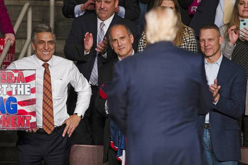 FILE - In this Dec. 15, 2016, file photo, U.S. Rep. Lou Barletta, R-Pa., left, U.S. Rep. Tom Marino, R-Pa., center left, and U.S. Rep. Scott Perry, R-Pa., right, watch as President-elect Donald Trump, center right, departs a rally in Hershey, Pa. Pennsylvania's highest court overstepped its authority in drawing new congressional district lines and did not give state lawmakers enough time to produce a map of their own, eight Republican congressmen said in a lawsuit filed Thursday, Feb. 22, 2018. (AP Photo/Matt Rourke, File)