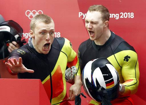 Driver Francesco Friedrich, right, and Thorsten Margis of Germany celebrate after they tied for the gold medal during the two-man bobsled final at the 2018 Winter Olympics in Pyeongchang, South Korea, Monday, Feb. 19, 2018. (AP Photo/Andy Wong)