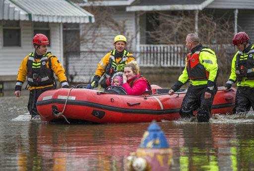 Firefighters use a raft to rescue Samantha Tucker, center, and her young child and infant, after rising flood waters submerged her home, Wednesday, Feb. 21, 2018, in South Bend, Ind. (Robert Franklin/South Bend Tribune via AP)