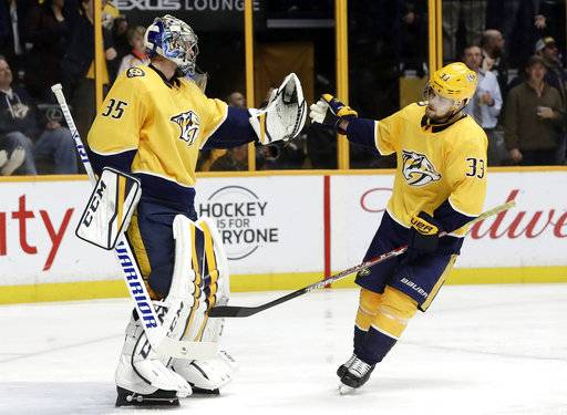 Nashville Predators left wing Viktor Arvidsson (33), of Sweden, is congratulated by goalie Pekka Rinne (35), of Finland, after Arvidsson scored a goal against the San Jose Sharks in the third period of an NHL hockey game Thursday, Feb. 22, 2018, in Nashville, Tenn. (AP Photo/Mark Humphrey)
