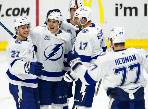 Tampa Bay Lightning center Brayden Point (21) celebrates his goal with teammates Yanni Gourde (37), Alex Killorn (17) and Victor Hedman (77) during the second period of an NHL hockey game Thursday, Feb. 22, 2018, in Ottawa, Ontario. (Adrian Wyld/The Canadian Press via AP)