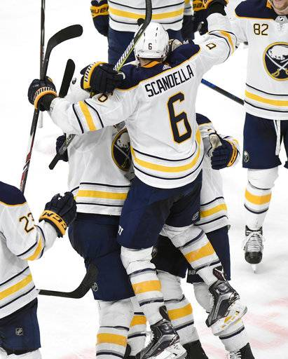 Buffalo Sabres defenseman Marco Scandella (6) leaps into the arms of center Ryan O'Reilly and center Scott Wilson after scoring in overtime against the Detroit Red Wings in an NHL hockey game, Thursday, Feb. 22, 2018, in Detroit. The Sabres won 3-2.