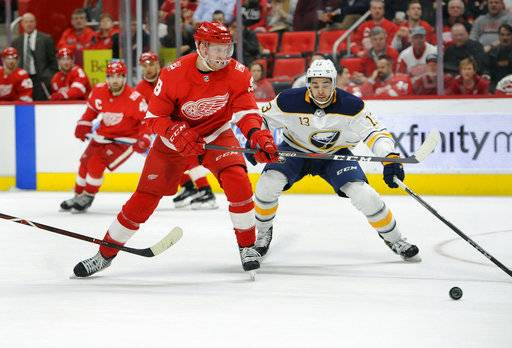Detroit Red Wings right wing Anthony Mantha (39) goes for the puck as he is chased by Buffalo Sabres right wing Nicholas Baptiste (13) during the second period of an NHL hockey game Thursday, Feb. 22, 2018, in Detroit.