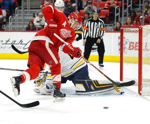 Detroit Red Wings left wing Justin Abdelkader (8) cannot reach the puck as Buffalo Sabres goaltender Robin Lehner (40) defends during the second period of an NHL hockey game Thursday, Feb. 22, 2018, in Detroit.