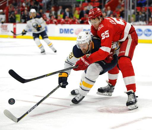 Buffalo Sabres center Zemgus Girgensons (28), of Latvia, and Detroit Red Wings defenseman Danny DeKeyser (65) vie for the puck during the first period of an NHL hockey game Thursday, Feb. 22, 2018, in Detroit.