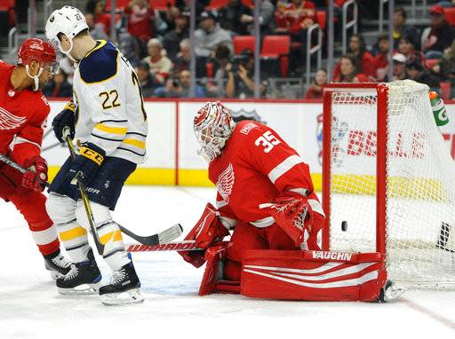 Buffalo Sabres center Johan Larsson (22), of Sweden, watches as the puck shot by defenseman Rasmus Ristolainen, of Finland, gets past Detroit Red Wings goaltender Jimmy Howard (35) during the first period of an NHL hockey game Thursday, Feb. 22, 2018, in Detroit.