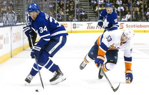 Toronto Maple Leafs' Auston Matthews, left, takes the puck away from New York Islanders' Casey Cizikas during second-period NHL hockey game action in Toronto on Thursday, Feb. 22, 2018. (Chris Young/The Canadian Press via AP)