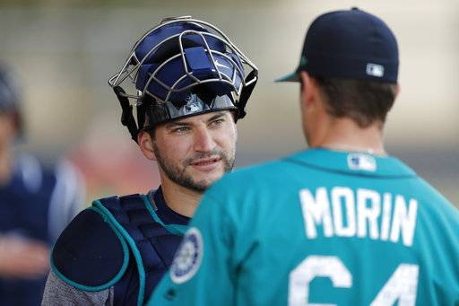 Seattle Mariners catcher Mike Zunino, left, talks with relief pitcher Mike Morin during a baseball spring training workout, Monday, Feb. 19, 2018, in Peoria, Ariz. (AP Photo/Charlie Neibergall)