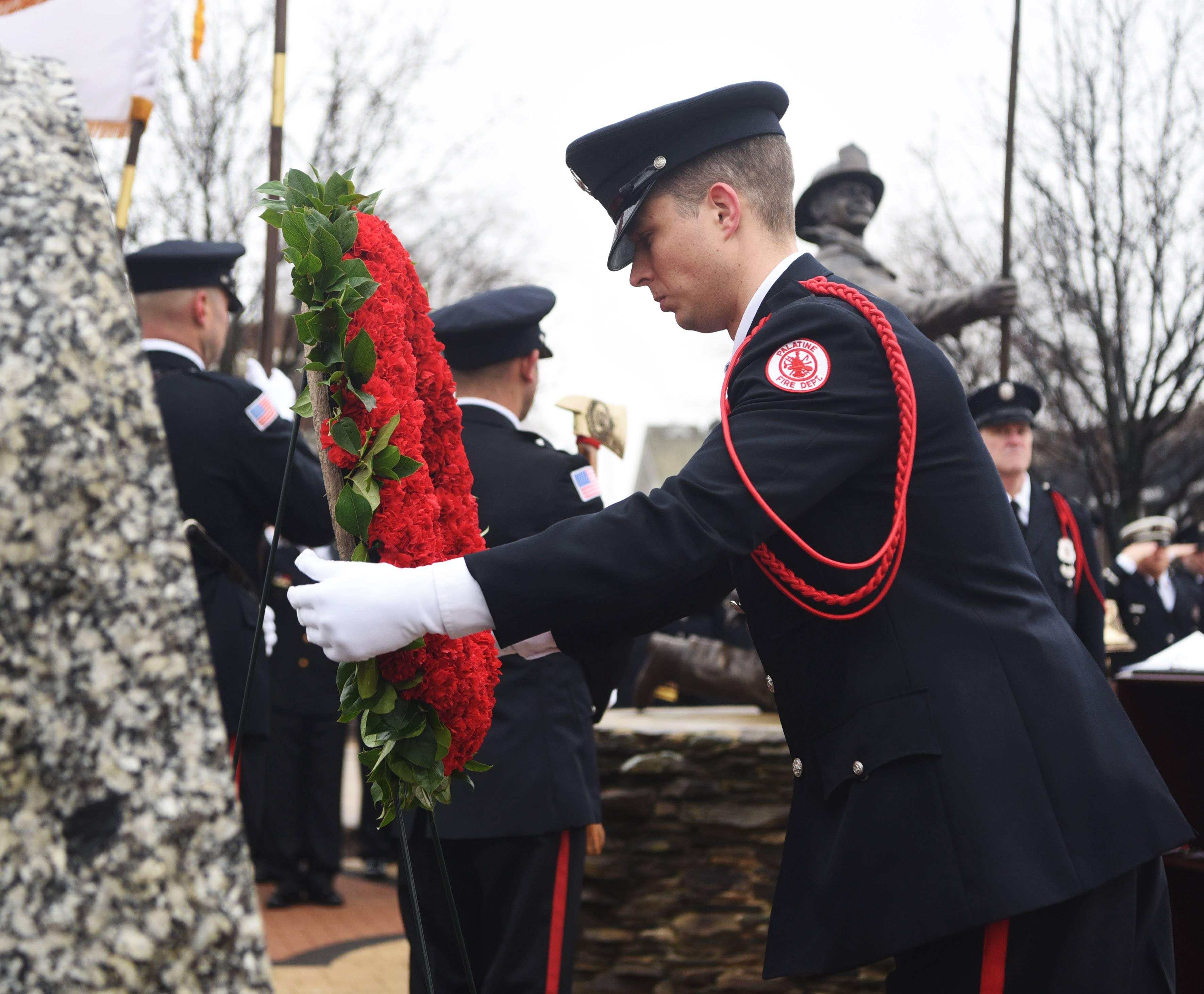 Firefighter/paramedic Brandon Lefebvre places a wreath during a ceremony to recognize the service and sacrifice of three Palatine volunteer firefighters who were killed in the line of duty while battling a Ben Franklin store fire on Feb. 23, 1973.