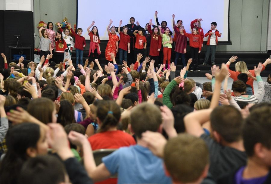 North Barrington Elementary School students wave along with a performance Friday during a Chinese New Year talent show at the school. Third grade students put on a show for fellow students in the afternoon, followed by a program for parents and family in the evening.
