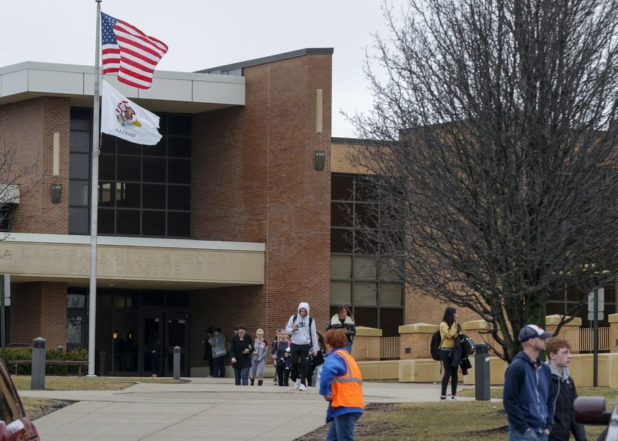 Students leave Lake Park High School on Friday morning after a social media threat caused administrators to cancel classes at both campuses in Roselle.
