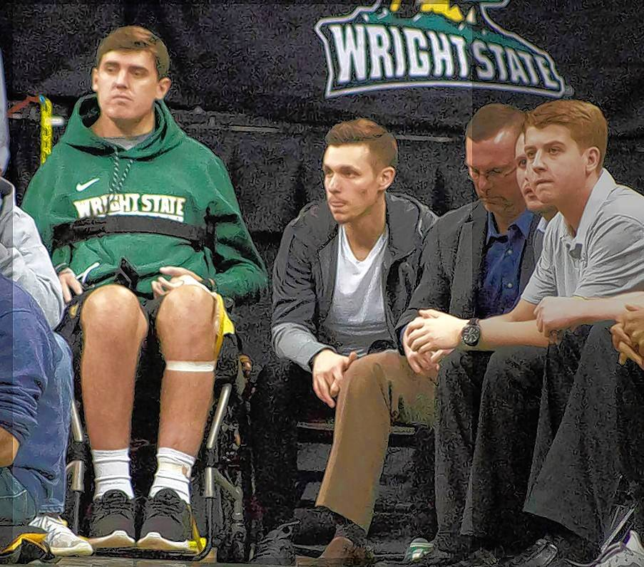 Former Wright State teammates Ryan Custer, in the wheelchair, and Mike LaTulip, to Custer's left in jacket and T-shirt, attend a recent basketball game at the Nutter Center in Fairborn, Ohio.