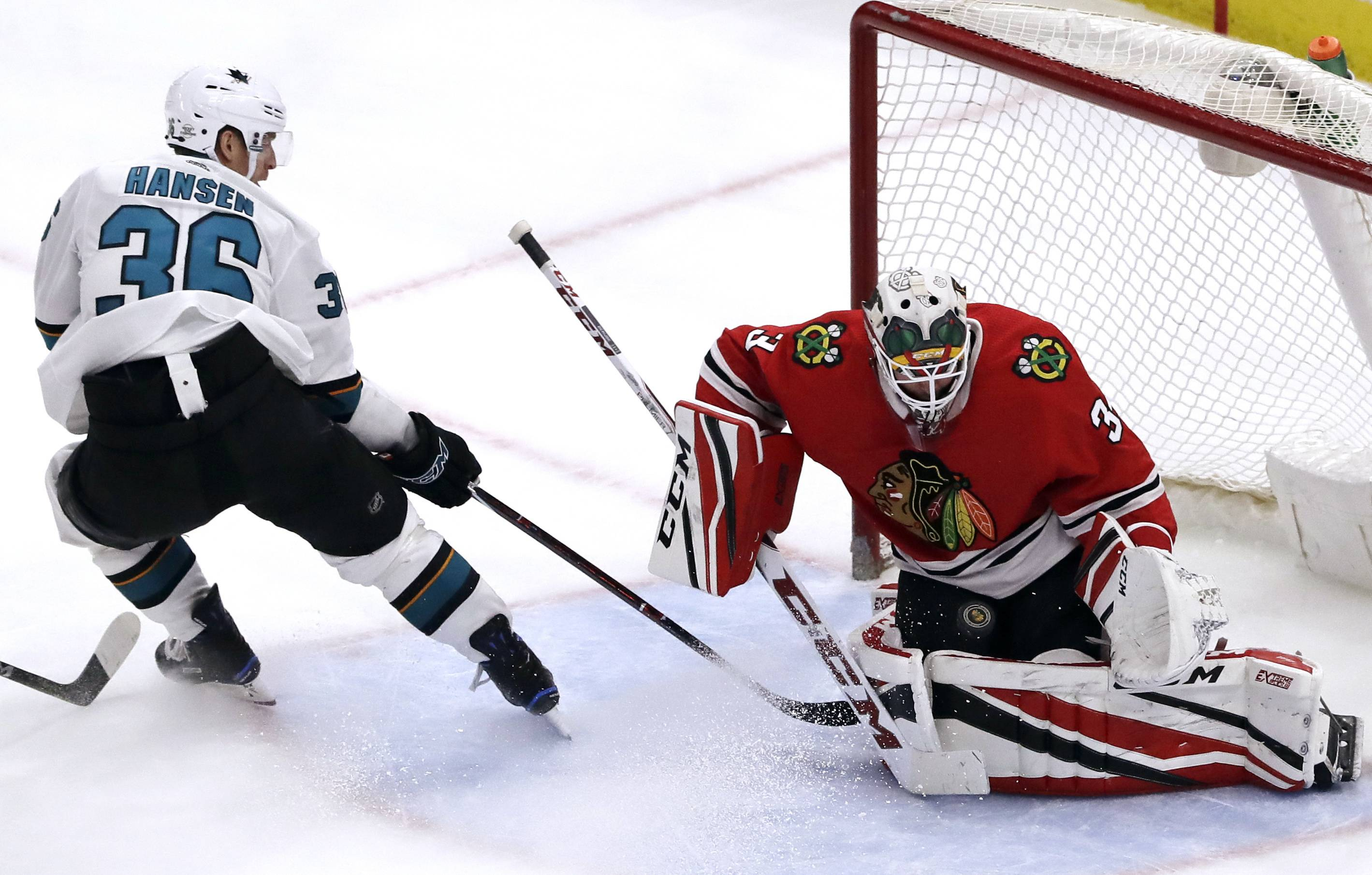 Chicago Blackhawks goalie J-F Berube, right, stops a shot by San Jose Sharks right wing Jannik Hansen during the third period Friday at the United Center. The Blackhawks won 3-1.