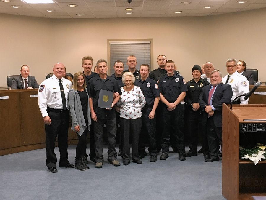 Mark Konicek, front row with award, poses with Wauconda Police Chief David Wermes, far left, and others after being honored for helping a choking woman. The woman he helped, Marge Wilhelm, is to his left.