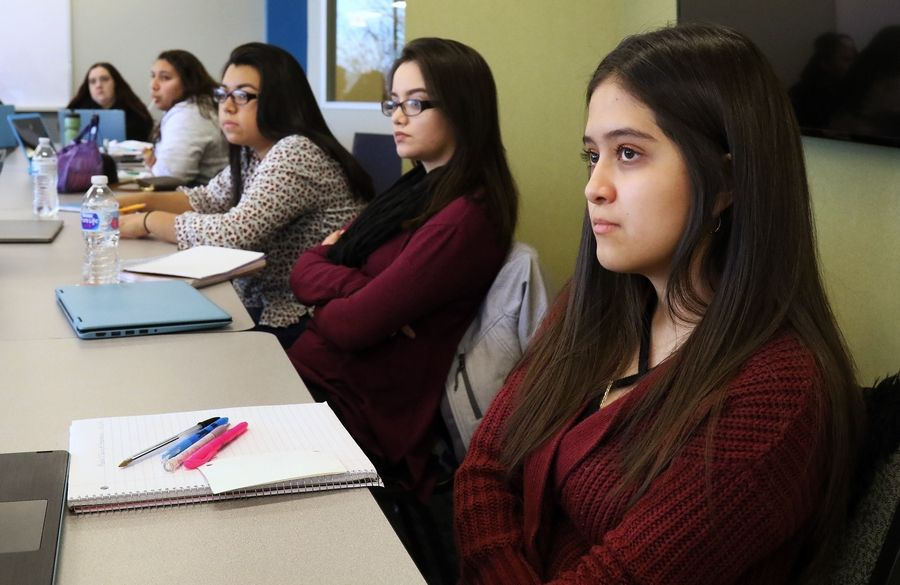"Students Paola Solis of Round Lake, right, and Alejandra Cisneros of Mundelein, both 18, listen to their instructor during an ""Effective Speaking"" class in the new Pathways program at National Louis University at Wheeling."
