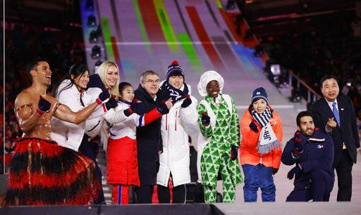 Athletes from various nations including Pita Taufatofua, of Tonga, at left, United States' Lindsey Vonn, third from left, and Thomas Bach, president of the International Olympic Committee, fifth from left, pose for photos during the closing ceremony of the 2018 Winter Olympics in Pyeongchang, South Korea, Sunday, Feb. 25, 2018.