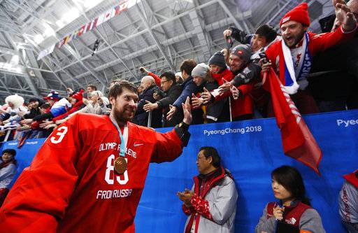 Olympic athlete from Russia Vasily Koshechkin celebrates with fans after winning the men's gold medal hockey game against Germany, 4-3, in overtime at the 2018 Winter Olympics, Sunday, Feb. 25, 2018, in Gangneung, South Korea.