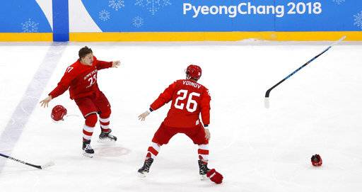 Russian athlete Kirill Kaprizov (77) and Vyacheslav Voynov (26) celebrate after winning the men's gold medal hockey game against Germany, 4-3, at the 2018 Winter Olympics, Sunday, Feb. 25, 2018, in Gangneung, South Korea.