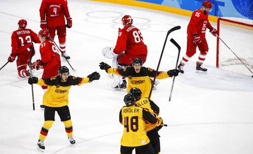 Dominik Kahun (72), of Germany, Frank Hördler (48), Jonas Muller (41) and Frank Mauer (28) celebrate after a goal by Mueller during the third period of the men's gold medal hockey game against the Olympic athletes from Russia at the 2018 Winter Olympics, Sunday, Feb. 25, 2018, in Gangneung, South Korea.