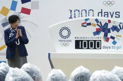 FILE - In this Oct. 28, 2017, file photo, Tokyo Gov. Yuriko Koike claps while looking at the day counter after it's unveiled during a Tokyo 2020 Olympics countdown event in Tokyo. Tokyo used its famous 1964 Olympics to show off a miraculous recovery from defeat in World War II. This time the Japanese capital will use the games to showcase a clean, safe, and innovative city with great shopping and nightlife.