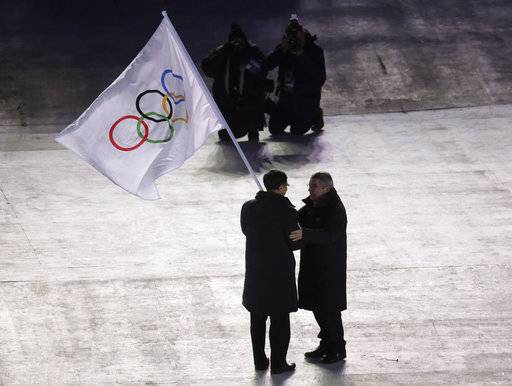 International Olympic Committee President Thomas Bach, right, hands the Olympic flag to the mayor of Beijing Chen Jining, during the closing ceremony of the 2018 Winter Olympics in Pyeongchang, South Korea, Sunday, Feb. 25, 2018.