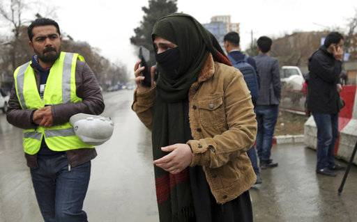 A woman talks to her phone as her relative were at site of a suicide bombing in the diplomatic area of capital Kabul, Afghanistan, Saturday, Feb. 24, 2018. Interior ministry spokesman Najib Danish said several people were wounded in Saturday's attack in the Shash Darak area of Kabul, near NATO headquarters and not far from the U.S. Embassy.