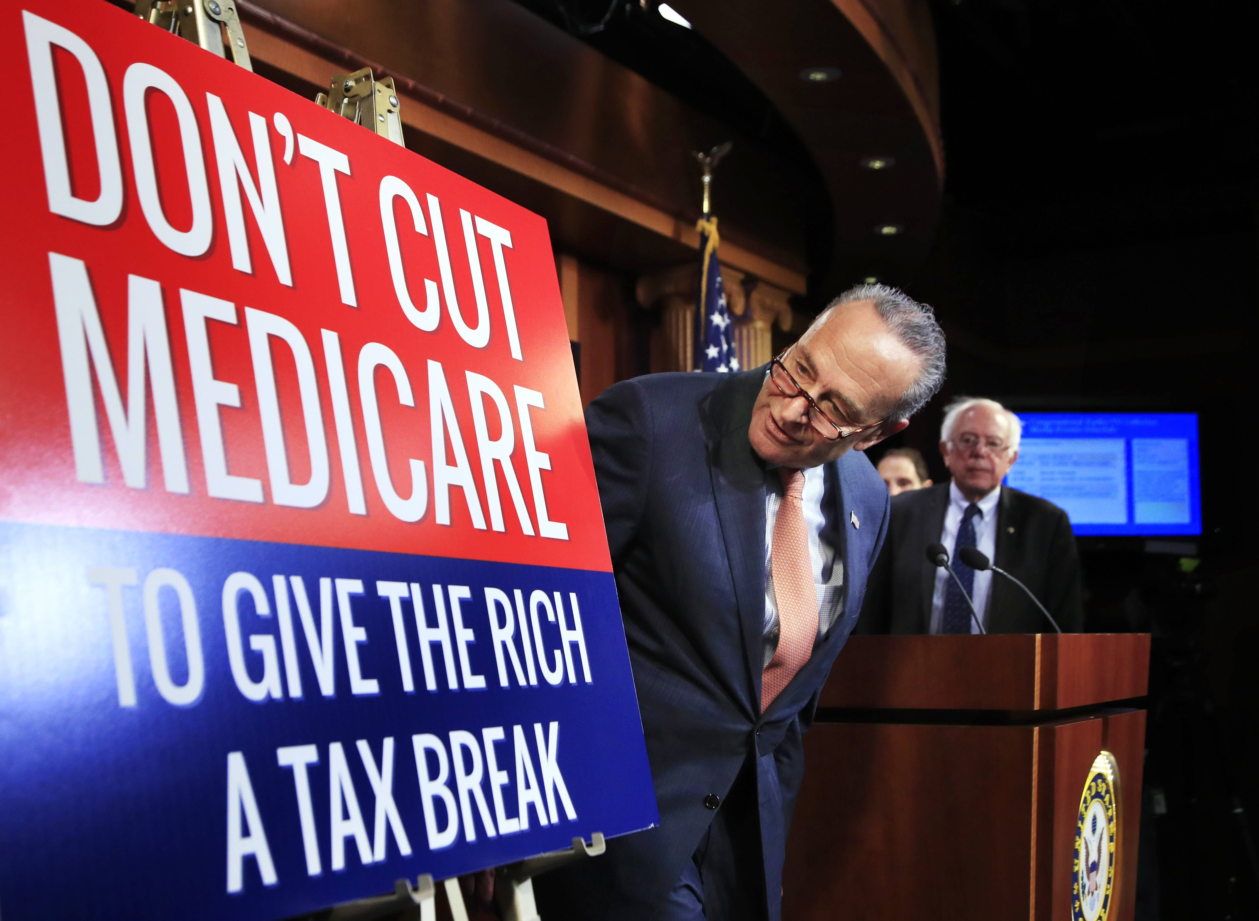 Senate Minority Leader Chuck Schumer of New York, followed by Sen. Bernie Sanders, I-Vt., look at a poster at the start of a news conference on Capitol Hill in Washington, Wednesday, October 4, 2017, urging Republicans to abandon cuts to Medicare and Medicaid.
