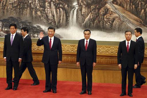 FILE - In this Oct 25, 2017, file photo, Chinese President Xi Jinping, third from left, waves near Chinese Premier Li Keqiang, third from right, as they walk in with other members of the Chinese Politburo Beijing's at the Great Hall of the People. On a proposal made public Sunday, Feb. 25, 2018, China's ruling Communist Party proposes removing a limit of two consecutive terms for the president and vice president.