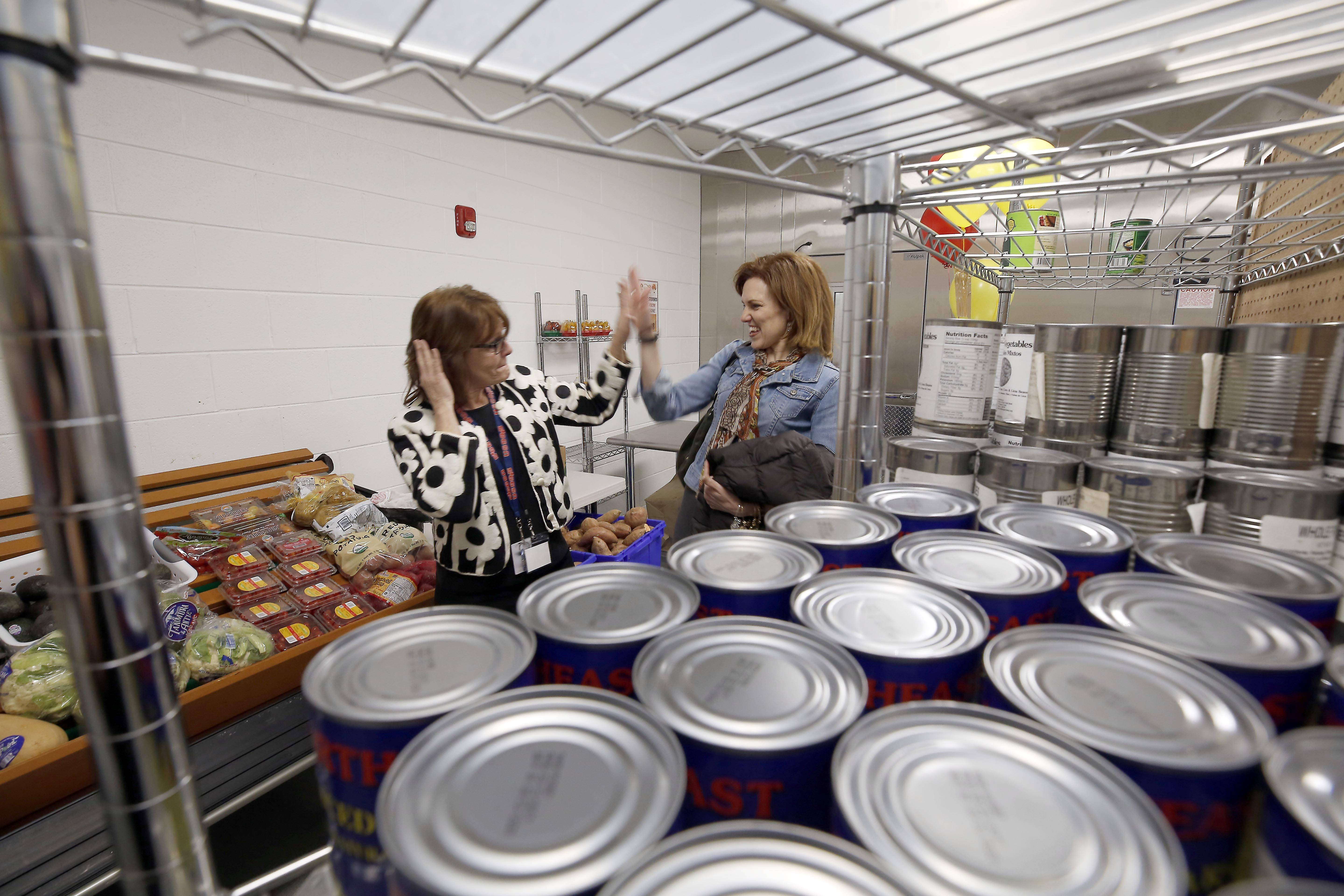 Diane Renner, left, director of the Marie Wilkinson Community Food Pantry at East Aurora High School, walks through the new location with Julie Yurko, president of the Northern Illinois Food Bank.