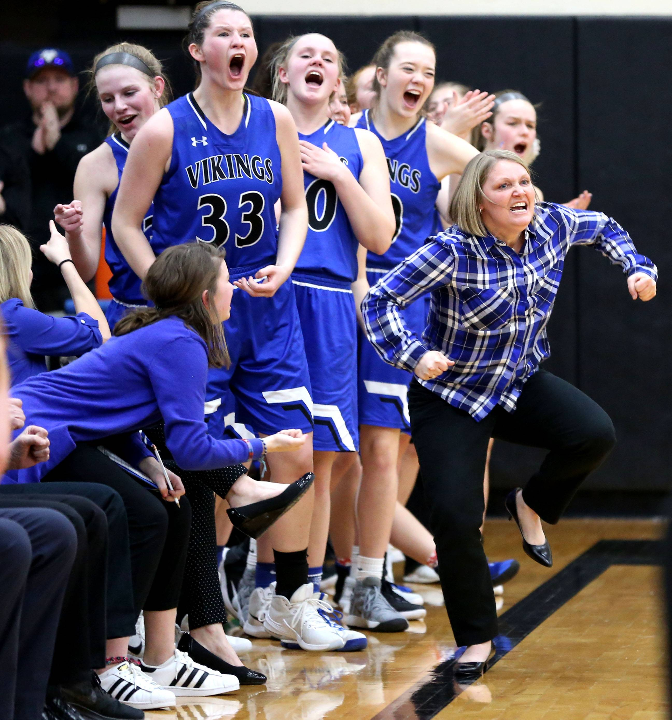 The Vikings of Geneva celebrate a supersectional girls basketball win over Rockford Boylan at Streamwood High School Monday night. Head coach Sarah Meadows gets revved up in the first half.