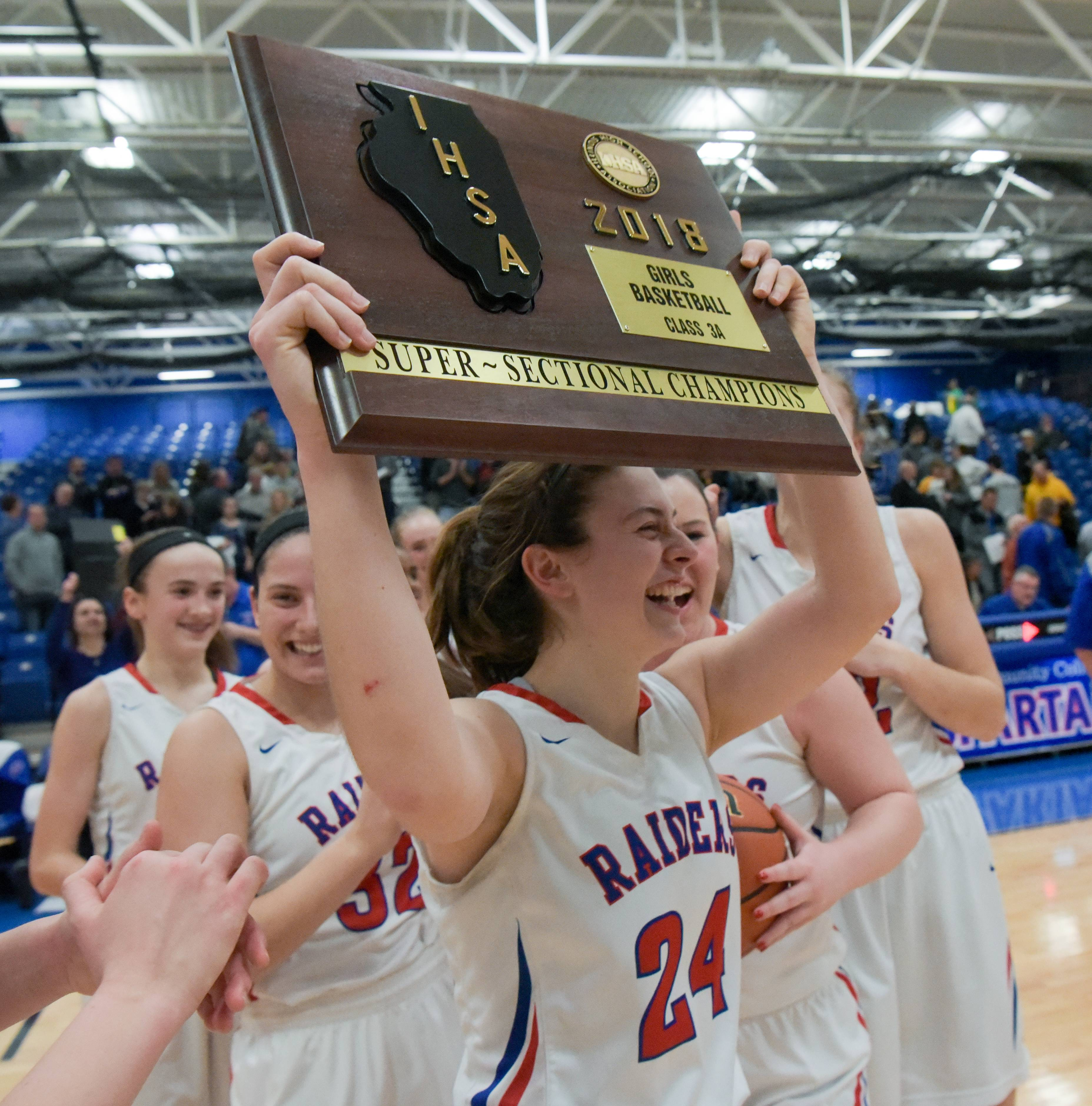 Glenbard South senior guard Sarah Cohen holds up the Class 3A supersectional championship plaque after defeating Carmel 48-33 on Monday, Feb. 26, at Elgin Community College.