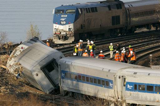 FILE - In a Dec. 1, 2013, file photo, an Amtrak train, top, traveling on an unaffected track, passes a derailed Metro North commuter train, in the Bronx borough of New York. President Donald Trump is putting the brakes on attempts to address dangerous transportation safety problems from speeding tractor-trailers to sleepy railroad engineers as part of his quest to roll back regulations across the government. (AP Photo/Mark Lennihan, File)