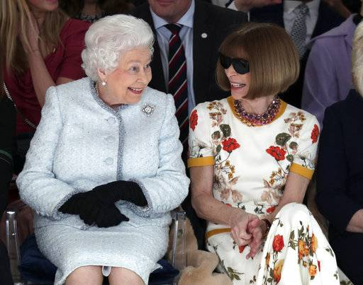 FILE - This is a Tuesday, Feb. 20, 2018 file photo of Britain's Queen Elizabeth as she sits next to fashion editor Anna Wintour as they view Richard Quinn's runway show before presenting him with the inaugural Queen Elizabeth II Award for British Design, as she visits London Fashion Week's BFC Show Space in central London (Yui Mok/ Pool photo/ File via AP)