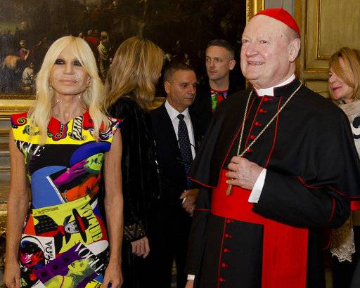 "Cardinal Gianfranco Ravasi and designer Donatella Versace arrive at Palazzo Colonna in Rome, Monday, Feb. 26, 2018. The Vatican is loaning some of its most beautiful liturgical vestments, jeweled miter caps and historic papal tiaras for an upcoming exhibit on Catholic influences in fashion at the Metropolitan Museum of Art. The Vatican culture minister, Cardinal Gianfranco Ravasi, joined Vogue Editor-in-Chief Anna Wintour and designer Donatella Versace in Rome on Monday to display a few of the Vatican treasures at the Palazzo Colonna, a onetime papal residence. ""Heavenly Bodies: Fashion and the Catholic Imagination"" is set to open May 10 at the Met's Costume Institute in New York. (AP Photo/Domenico Stinellis)"