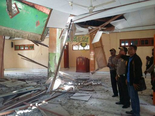 In this photo released on Tuesday, Feb. 27, 2018, by Indonesia's National Disaster Mitigation Agency (BNPB), local officials inspect the damage to a mosque following monday's powerful earthquake in neighboring Papua New Guinea, in Boven Digoel, Papua province, Indonesia. Severe damage to phone networks and roads from the earthquake in Papua New Guinea was hindering efforts to assess the extent of the destruction Tuesday, although officials in the remote central region fear dozens of people may have been injured or killed. (BNPB via AP)