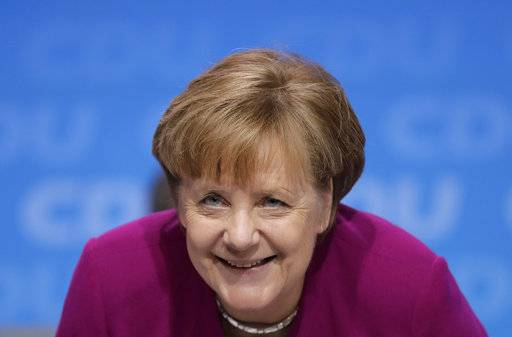 German Chancellor and party chairwoman Angela Merkel smiles at the party convention of the Christian Democratic Union CDU in Berlin, Germany, Monday, Feb. 26, 2018. The delegates voted for the coalition agreement on forming a new German government. (AP Photo/Markus Schreiber)