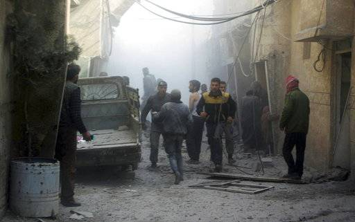 This photo released on Saturday, Feb 24, 2018 by the Syrian Civil Defense group known as the White Helmets, shows members of the Syrian Civil Defense group and civilians gathering to help survivors from a street attacked by airstrikes and shelling by Syrian government forces, in Ghouta, a suburb of Damascus, Syria. A new wave of airstrikes and shelling on eastern suburbs of the Syrian capital Damascus left at least 22 people dead and more than a dozen wounded Saturday, raising the death toll of a week of bombing in the area to nearly 500, including scores of women and children. (Syrian Civil Defense White Helmets via AP)