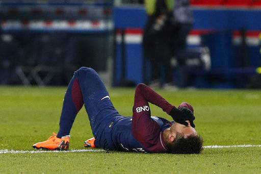 PSG's Neymar lays on the pitch after being fouled during the French League One soccer match between Paris Saint-Germain and Marseille at the Parc des Princes Stadium, in Paris, France, Sunday, Feb. 25, 2018. (AP Photo/Thibault Camus)