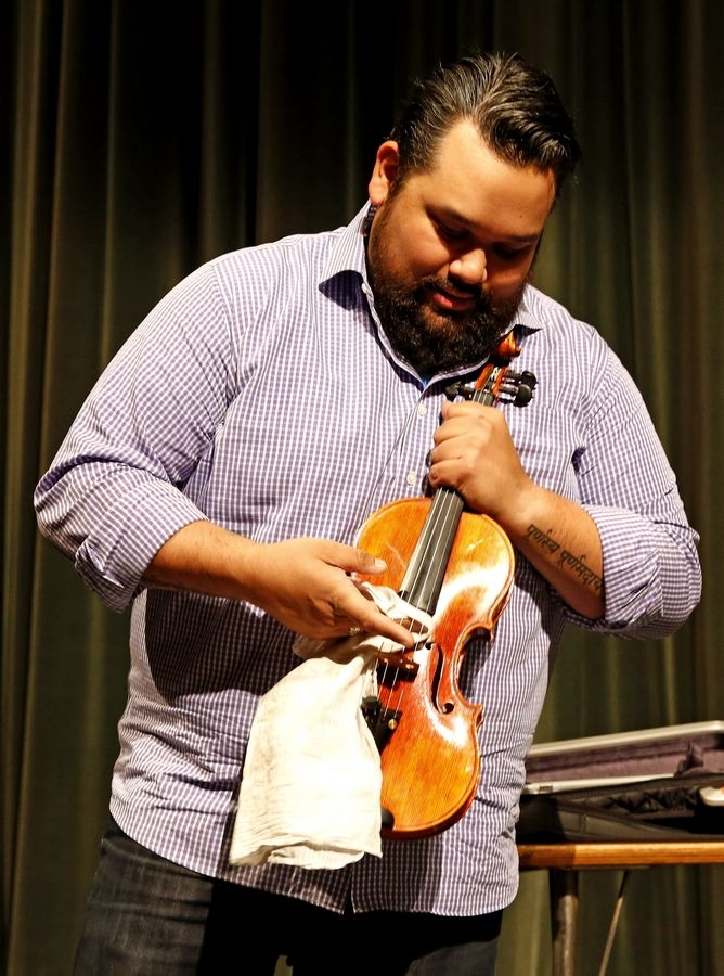 "Vijay Gupta, founder of Street Symphony and violinist with the Los Angeles Philharmonic, talks about the healing power of music Tuesday to students at Waubonsie Valley High School in Aurora. ""I give you the same message that I was given, which is that you need to do what makes you leap out of bed in the morning,"" Gupta said. ""That's the only thing you have to do. You owe it to yourselves."""