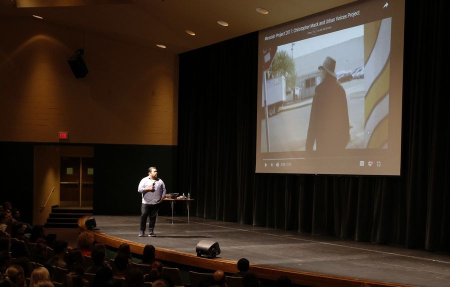 Vijay Gupta, founder of Street Symphony and violinist with the Los Angeles Philharmonic orchestra, shows a video Tuesday of his mentor, Christopher Mack and the Urban Voices Project, as he gives a talk and performance at Waubonsie Valley High School in Aurora.