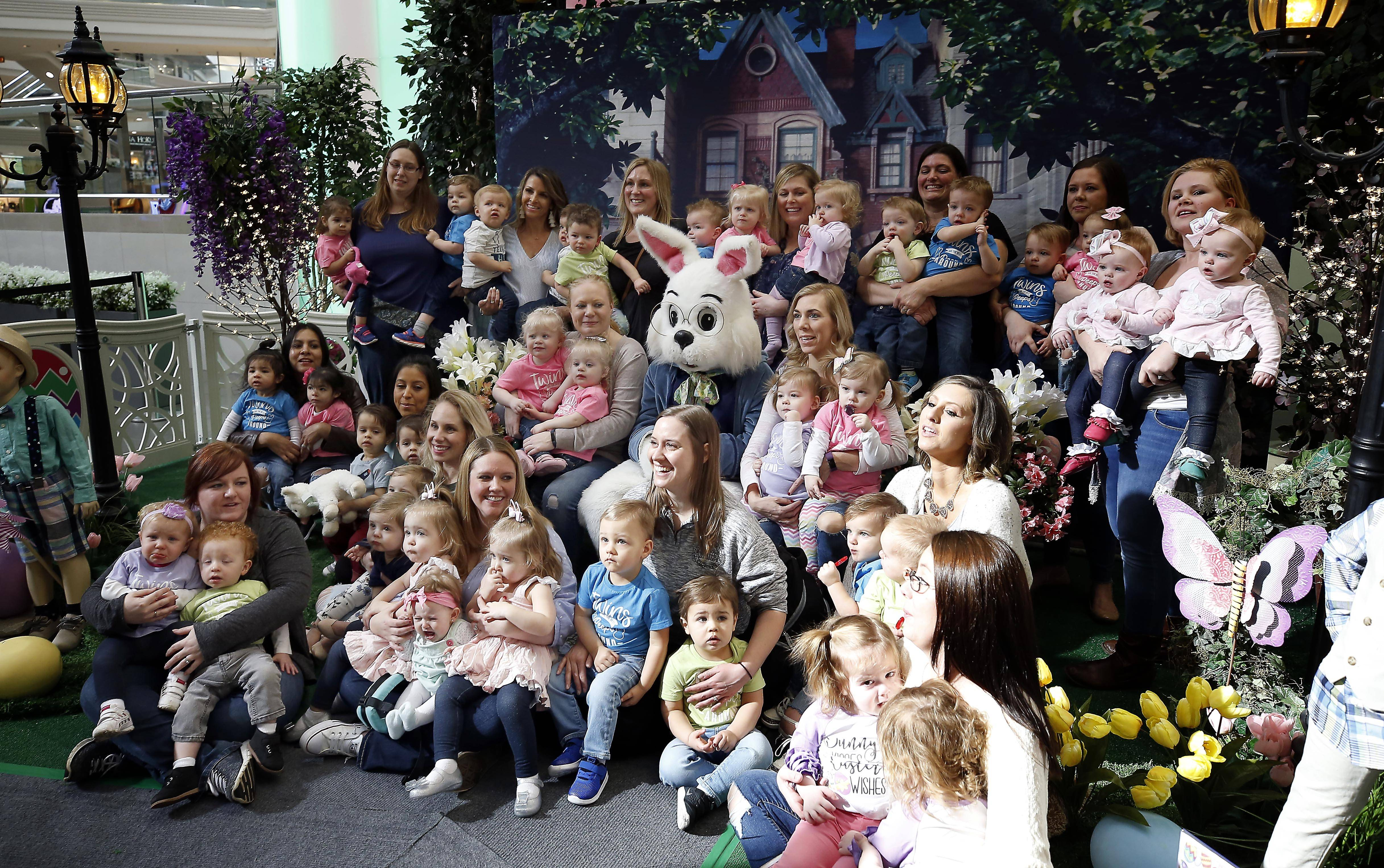 "Eighteen sets of twins, all under the age of 2, dressed in their Easter best Tuesday morning for a group photo with the Easter Bunny at Woodfield Mall in Schaumburg. ""We'll probably need a mom's night out after this,"" joked Dee Knoll of Arlington Heights, co-founder of the mom's group that organized the photo."