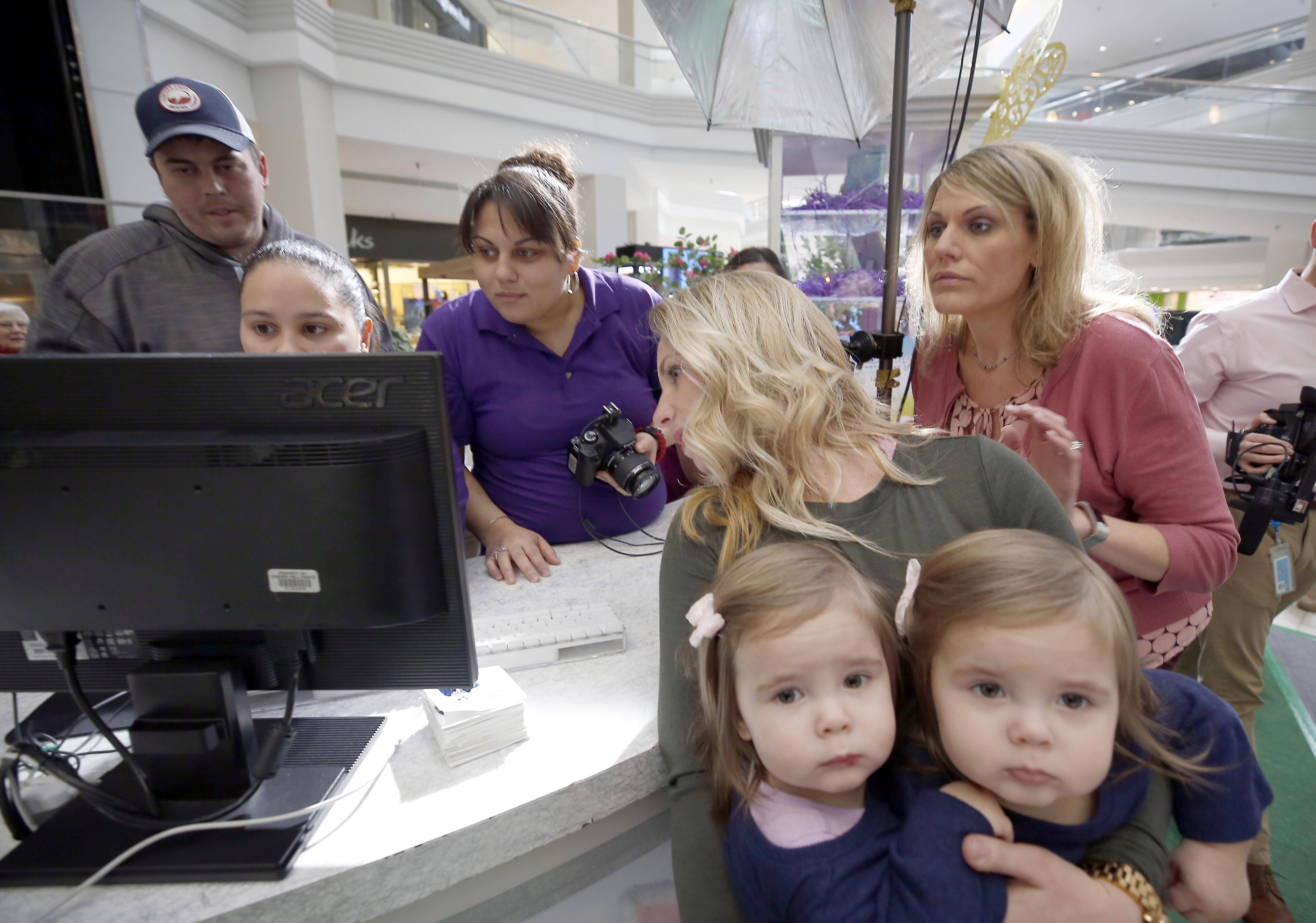 Miranda Marshall of Crystal Lake holds 18-month-old twins Ainsley and Emersyn while she looks at the group photo of 18 sets of twins, all under the age of 2, with the Easter Bunny Tuesday at Woodfield Mall in Schaumburg. District Manager of Cherry Hill Programs, Michele Colorato, is pictured far right, Manager Karina Zabeleta works the computer and Jeannette Gonzalez is holding the camera.
